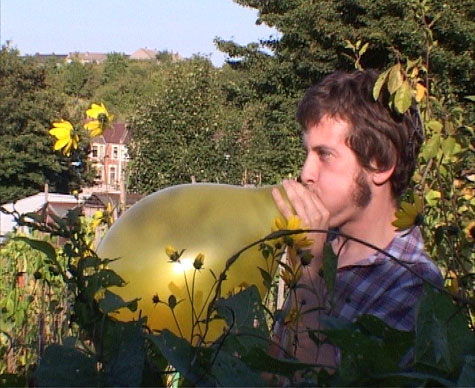 a man standing behind a hedge blowing up a yellow balloon