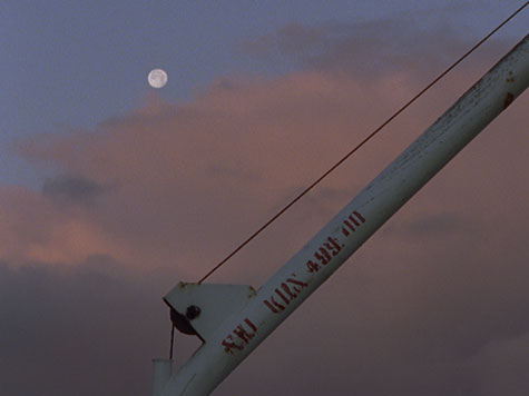 Ships mast at dusk with pink clouds and the moon in background