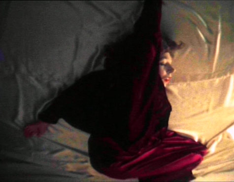 image of a woman lying on a bed in a strange possition wearing a red dressing gown