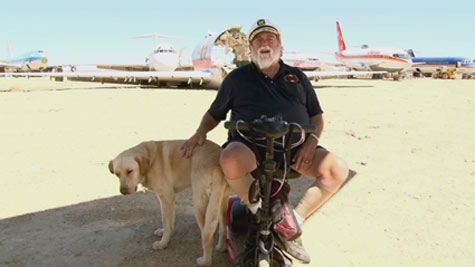elderly man sitting in front of old aircraft
