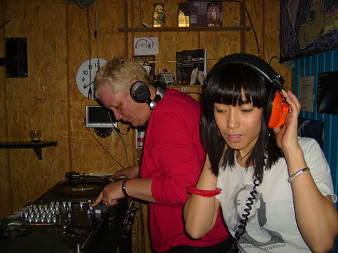 two female DJs at a club, one on decks, one with headphones