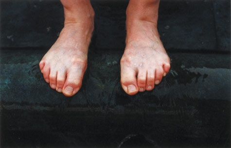 photograph of bare feet on edge of a step