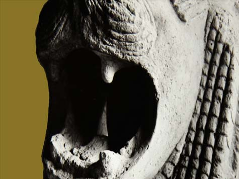close up of an antique statue of a roaring lion on an ochre background