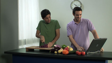 two men chatting and chopping vegetables while looking at a laptop