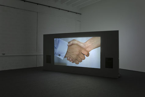 projector screen with image of hands shaking