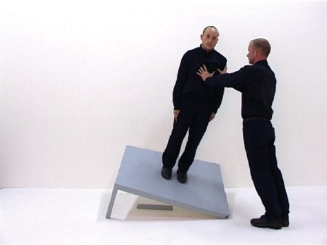 a man on a unbalanced table, being supported by another man